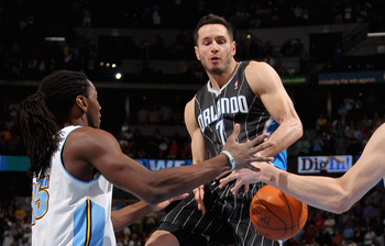 DENVER, CO - APRIL 22:  J.J. Redick #7 of the Orlando Magic looses control of the ball against the defense of Kenneth Faried #35 and Kosta Koufos #41 of the Denver Nuggets at Pepsi Center on April 22, 2012 in Denver, Colorado. NOTE TO USER: User expressly