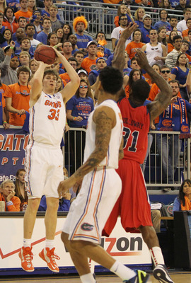 February 2, 2013; Gainesville, FL, USA; Florida Gators forward/center Erik Murphy (33) shoots a three-pointer as Ole Miss Rebels forward Murphy Holloway (31) attempted to defend during the first half at the Stephen C. O'Connell Center. Mandatory USA TODAY