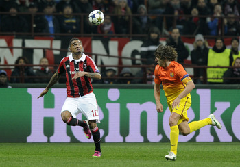 MILAN, ITALY - FEBRUARY 20:  Carles Puyol of FC Barcelona compete for the ball with Kevin Prince Boateng of AC Milan (L) compete for the ball during the UEFA Champions League Round of 16 first leg match between AC Milan and Barcelona at San Siro Stadium o