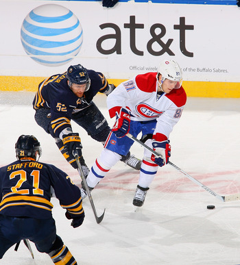 Lars Eller against Drew Stafford (left) and Alexander Sulzer of the Buffalo Sabres.