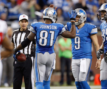 DETROIT, MI - DECEMBER 22:  Calvin Johnson #81 of the Detroit Lions celebrates a 26-yard fourth quarter catch with Matthew Stafford #9 while playing the Atlanta Falcons at Ford Field on December 22, 2012 in Detroit, Michigan.  Johnson broke the NFL single