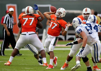 Nov 5, 2011; Miami Gardens, FL, USA;  Miami Hurricanes quarterback Stephen Morris (17) passes the ball against the Duke Blue Devils with blocking from Hurricanes offensive linesman Seantrel Henderson (77) Sun Life Stadium. Mandatory Credit: Robert Mayer-U