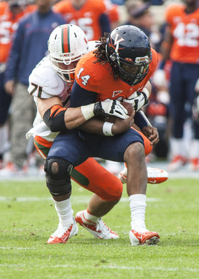 Nov 10, 2012; Charlottesville, VA, USA; Virginia Cavaliers quarterback Phillip Sims (14) is sacked by Miami Hurricanes defensive lineman Anthony Chickillo (71) at Scott Stadium. Mandatory Credit: Peter Casey-USA TODAY Sports