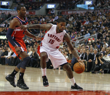 Feb 25, 2013; Toronto, Ontario, CAN; Toronto Raptors center-forward Amir Johnson (15) carries the ball past Washington Wizards guard John Wall (2) during the first half at the Air Canada Centre. Mandatory Credit: John E. Sokolowski-USA TODAY Sports