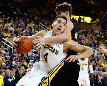 ANN ARBOR, MI - JANUARY 06:  Mitch McGary #4 of the Michigan Wolverines tries to get around the arm of Adam Woodbury #34 of the Iowa Hawkeyes during the first half at Crisler Center on January 6, 2013 in Ann Arbor, Michigan. Michigan won the game 95-67.