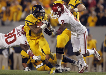West Virginia's Tavon Austin bulls through tacklers in a game against Oklahoma, Nov. 17.