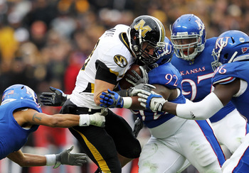 Missouri's T.J. Moe fends off tacklers in a game against Kansas, November 26, 2011.