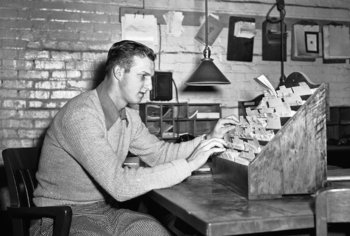 Stan Musial checking paperwork at the Christmas Tree lot in 1943. Photo courtesy of NYTimes.com.