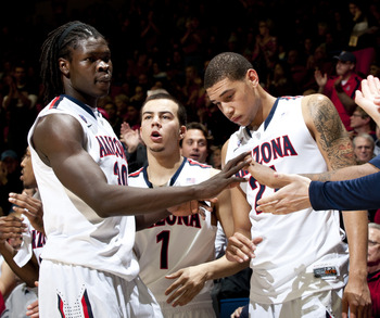 Feb 20, 2013; Tucson, AZ, USA; Arizona Wildcats guard Gabe York (1) and forward Brandon Ashley (21) greet forward Angelo Chol (30) as he returns to the bench during the second half against the Washington Huskies at McKale Center. Arizona beat Washington 7