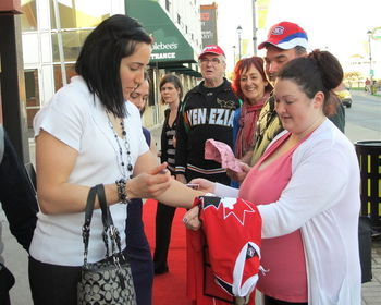 Ouellette (left) signing an autograph for a fan, Photo by Tony Ricciuto, Obtained from: http://www.niagarafallsreview.ca/2012/03/21/clarkson-cup-hockey-players-meet-fans-in-niagara-falls