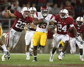 STANFORD, CA - NOVEMBER 15:  Stafon Johnson #13 of USC Trojans runs against Bo McNally #22 and Kris Evans #24 of the Stanford Cardinals in the first half at Stanford Stadium on November 15, 2008 in Stanford, California.  (Photo by Jed Jacobsohn/Getty Imag