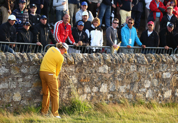 Angel Jimenez plays a shot off the wall next to the 17th green at the Old Course at St. Andrews.