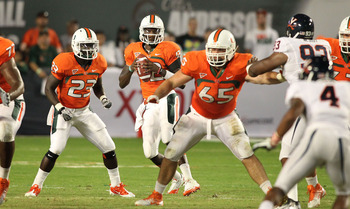 Oct 27, 2011; Miami Gardens, FL, USA;  Miami Hurricanes quarterback Jacory Harris (12) drops back to pass with blocking from running back Eduardo Clements (23) and offensive lineman Brandon Linder (65) during the game against the Virginia Cavaliers at Sun