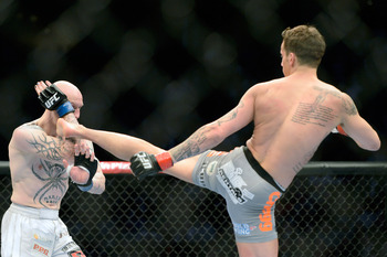 Mar 16, 2013; Montreal, Quebec, CAN;  Mike Ricci (red gloves) lands a kick on Colin Fletcher (blue) during their main card bout at UFC 158 at the Bell Centre. Mandatory Credit: Eric Bolte-USA TODAY Sports