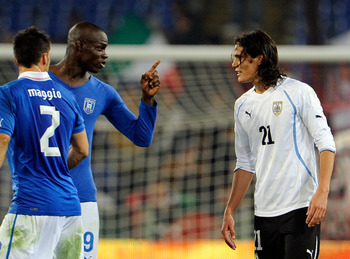 Uruguay striker Edinson Cavani (right) is confronted by Mario Balotelli during a 2011 friendly against Italy.