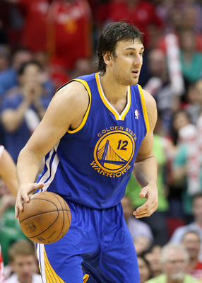 Mar 17, 2013; Houston, TX, USA; Golden State Warriors center Andrew Bogut (12) controls the ball during the third quarter against the Houston Rockets at Toyota Center. Mandatory Credit: Troy Taormina-USA TODAY Sports