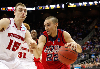 KANSAS CITY, MO - MARCH 22:  Marshall Henderson #22 of the Ole Miss Rebels drives against Sam Dekker #15 of the Wisconsin Badgers in the first half during the second round of the 2013 NCAA Men's Basketball Tournament at the Sprint Center on March 22, 2013
