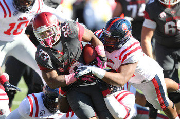 Oct 27, 2012; Little Rock, AR, USA; Arkansas Razorbacks running back Dennis Johnson (33) is tackled by Ole Miss Rebels defensive lineman Issac Gross (94) at War Memorial Stadium. Mississippi defeated Arkansas 30-27. Mandatory Credit: Nelson Chenault-USA T
