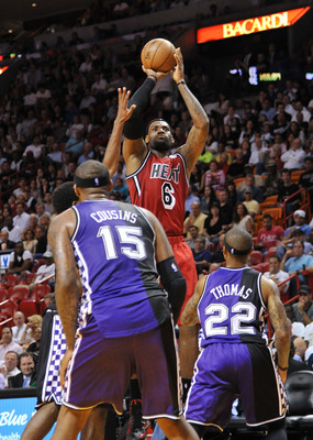 Feb 26, 2013; Miami, FL, USA; Miami Heat small forward LeBron James (6) shoots past Sacramento Kings center DeMarcus Cousins (15) and Sacramento Kings point guard Isaiah Thomas (22) during the second half at the American Airlines Arena. The Heat won in a