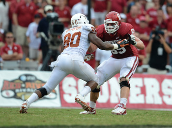 Oct 13, 2012; Dallas, TX, USA; Oklahoma Sooner tackle Lane Johnson (69) in action against Texas Longhorns defensive end Alex Okafor (80) during the red river rivalry at the Cotton Bowl. Mandatory Credit: Matthew Emmons-USA TODAY Sports