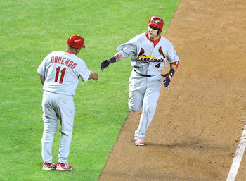 Third-base coach Jose Oquendo congratulates Yadier Molina after smashing a home run against Arizona, Wednesday night.