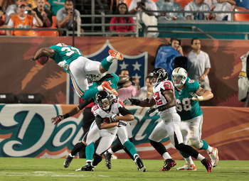 August 24, 2012; Miami Gardens, FL, USA; Miami Dolphins running back Daniel Thomas (33) leaps over Atlanta Falcons defensive back Brent Grimes (20) in the third quarter at Sun Life Stadium. Mandatory Credit: Robert Mayer-USA TODAY Sports