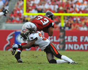 TAMPA, FL - SEPTEMBER 25:  Cornerback EJ. Biggers #31 of the Tampa Bay Buccaneers tackles running back Michael Turner #33 of the Atlanta Falcons September 25, 2011 at Raymond James Stadium in Tampa, Florida. (Photo by Al Messerschmidt/Getty Images)