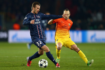 Andres Iniesta moves in on PSG's David Beckham.