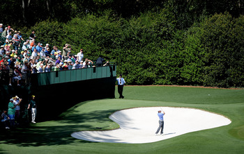 Rory McIlroy hits a practice shot from the greenside bunker at Augusta National's fourth hole.
