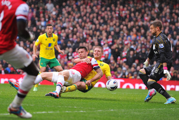 LONDON, ENGLAND - APRIL 13:  Michael Turner of Norwich City takes down Olivier Giroud of Arsenal during the Barclays Premier League match between Arsenal and Norwich City at Emirates Stadium on April 13, 2013 in London, England. (Photo by Mike Hewitt/Gett