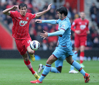 SOUTHAMPTON, ENGLAND - APRIL 13:  James Tomkins of West Ham tries to tackle Jack Cork of Southampton during the Barclays Premier League match between Southampton and West Ham United at St Mary's Stadium on April 13, 2013 in Southampton, England.  (Photo b
