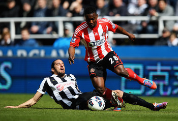 NEWCASTLE UPON TYNE, ENGLAND - APRIL 14:  Stephane Sessegnon of Sunderland beats the challenge from Jonas Gutierrez of Newcastle United during the Barclays Premier League match between Newcastle United and Sunderland at St James' Park on April 14, 2013 in
