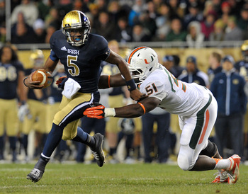 Oct. 6, 2012; Chicago, IL, USA; Notre Dame Fighting Irish quarterback Everett Golson (5) is pressured by Miami Hurricanes defensive end Shayon Green (51) in the second quarter at Soldier Field. Mandatory Credit: Matt Cashore-USA TODAY Sports
