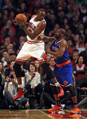 CHICAGO, IL - APRIL 11: Loul Deng #9 of the Chicago Bulls rebounds over Raymond Felton #2 of the New York Knicks at the United Center on April 11, 2013 in Chicago, Illinois. The Bulls defeated the Knicks 118-111 in overtime. NOTE TO USER: User expressly a