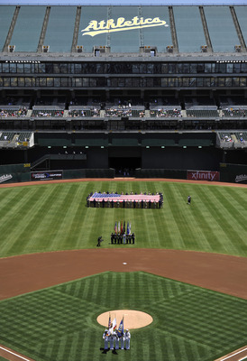 OAKLAND, CA - JULY 4:  A large American flag is held by 40 people in centerfield in celebration of Independence Day prior to the MLB game between the Seattle Mariners and Oakland Athletics at Oakland-Alameda County Coliseum on July 4, 2011 in Oakland, Cal