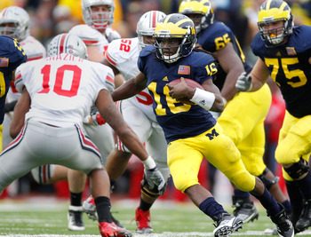 ANN ARBOR, MI - NOVEMBER 26: Denard Robinson #16 of the Michigan Wolverines tries to get around the tackle of Ryan Shazier #10 of the Ohio State Buckeyes at Michigan Stadium on November 26, 2011 in Ann Arbor, Michigan. Michigan won the game 40-34. (Photo