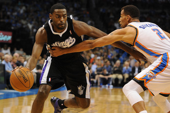 Apr 15, 2013; Oklahoma City, OK, USA; Sacramento Kings guard Tyreke Evans (13) handles the ball against Oklahoma City Thunder guard Thabo Sefolosha (2) during the first half at Chesapeake Energy Arena. Mandatory Credit: Mark D. Smith-USA TODAY Sports