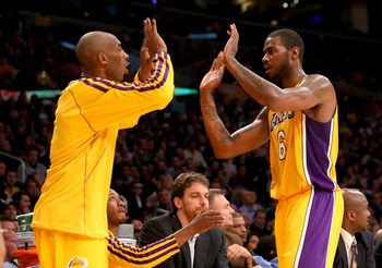 Kobe Bryant encourages the energy play of Earl Clark.