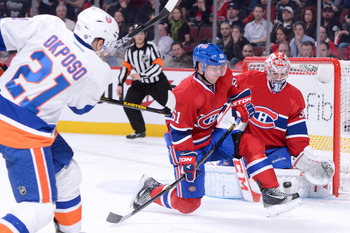 New York Islander Kyle Okposo (from left) takes a shot in front of Montreal Canadiens Raphael Diaz and Carey Price.