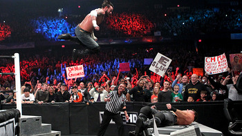 CM Punk drops an elbow drop on Chris Jericho at Extreme Rules 2012. Courtesy: wwe.com.