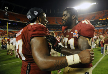 Jan 1, 2013; Miami Gardens, FL, USA; Florida State Seminoles safety Philip Doumar (57) and offensive linesman Menelik Watson (71) react following the win over the Northern Illinois Huskies at the 2013 Orange Bowl at Sun Life Stadium. The Seminoles defeate