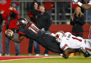 PISCATAWAY, NJ - NOVEMBER 29: Tight end D.C. Jefferson #10 of the Rutgers Scarlet Knights is tackled in the end zone by Keith Brown #1 of the Louisville Cardinals after a pass on a fake punt during the second half in a game at High Point Solutions Stadium