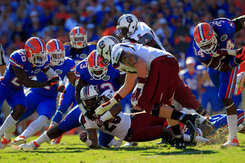 GAINESVILLE, FL - OCTOBER 20:  Running back Mike Davis #28 of the South Carolina Gamecocks is tackled by defensive lineman Sharrif Floyd #73 of the Florida Gators at Ben Hill Griffin Stadium on October 20, 2012 in Gainesville, Florida.  (Photo by Chris Tr