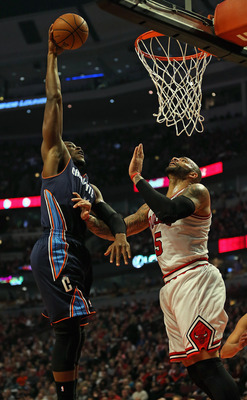 CHICAGO, IL - DECEMBER 31: Jeff Adrien #4 of the Charlotte Bobcats dunks the ball over Carlos Boozer #5 of the Chicago Bulls at the United Center on December 31, 2012 in Chicago, Illinois. NOTE TO USER: User expressly acknowledges and agrees that, by down