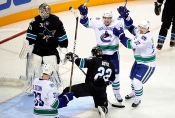 Henrik Sedin (#33) celebrates a goal with Daniel Sedin and Alex Burrows
