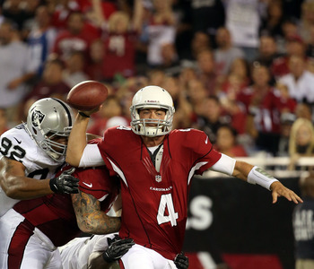 GLENDALE, AZ - AUGUST 17:  Quarterback Kevin Kolb #4 of the Arizona Cardinals throws away a pass as he is pressured by defensive end Richard Seymour #92 of the Oakland Raiders during the first half of the NFL preseason game at the University of Phoenix St