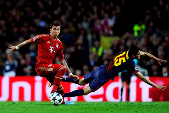 BARCELONA, SPAIN - MAY 01:  Mario Mandzukic of Munich and Marc Bartra of Barcelona compete for the ball during the UEFA Champions League semi final second leg match between Barcelona and FC Bayern Muenchen at Nou Camp on May 1, 2013 in Barcelona, Spain.