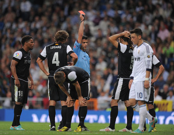 MADRID, SPAIN - MAY 08:  Referee Jesus Gil Manzano shows the red card to Martin Demichelis (2.R) of Malaga CF during the La Liga match between Real Madrid CF and Malaga CF at estadio Santiago Bernabeu on May 8, 2013 in Madrid, Spain.  (Photo by Denis Doyl
