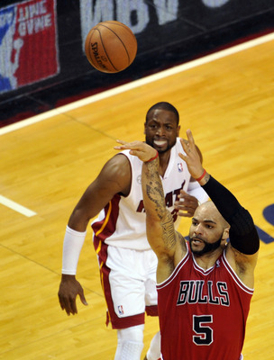 May 8, 2013; Miami, FL, USA; Chicago Bulls power forward Carlos Boozer (5) shoots as Miami Heat shooting guard Dwyane Wade (3) defends during the second quarter in game two of the second round of the 2013 NBA Playoffs at American Airlines Arena. Mandatory