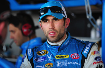 RICHMOND, VA - APRIL 26:  Aric Almirola, driver of the #43 Smithfield Ford, stands in the garage during practice for the NASCAR Sprint Cup Series Toyota Owners 400 at Richmond International Raceway on April 26, 2013 in Richmond, Virginia.  (Photo by Rober